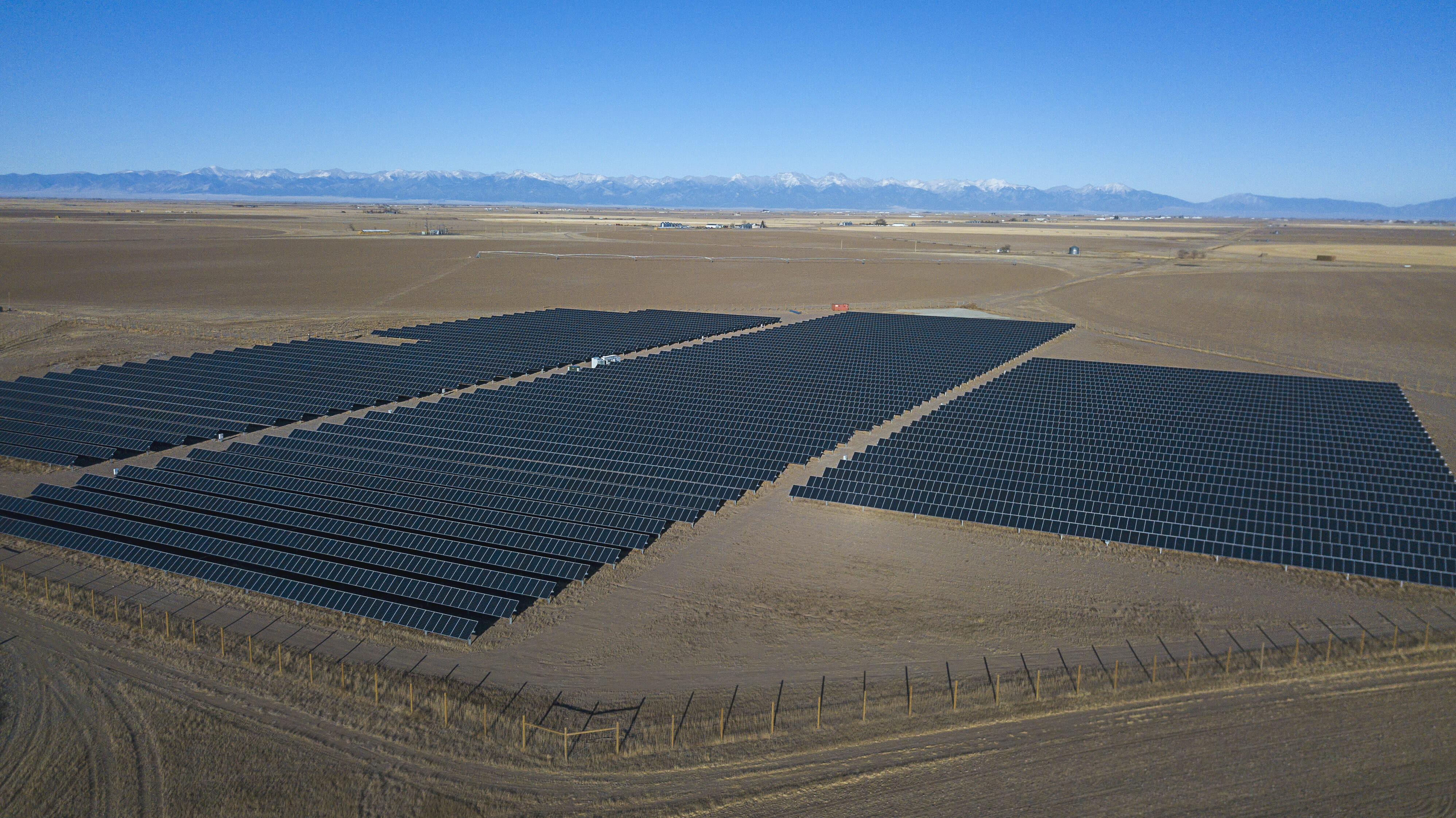 large commercial solar project with rocky mountains in background