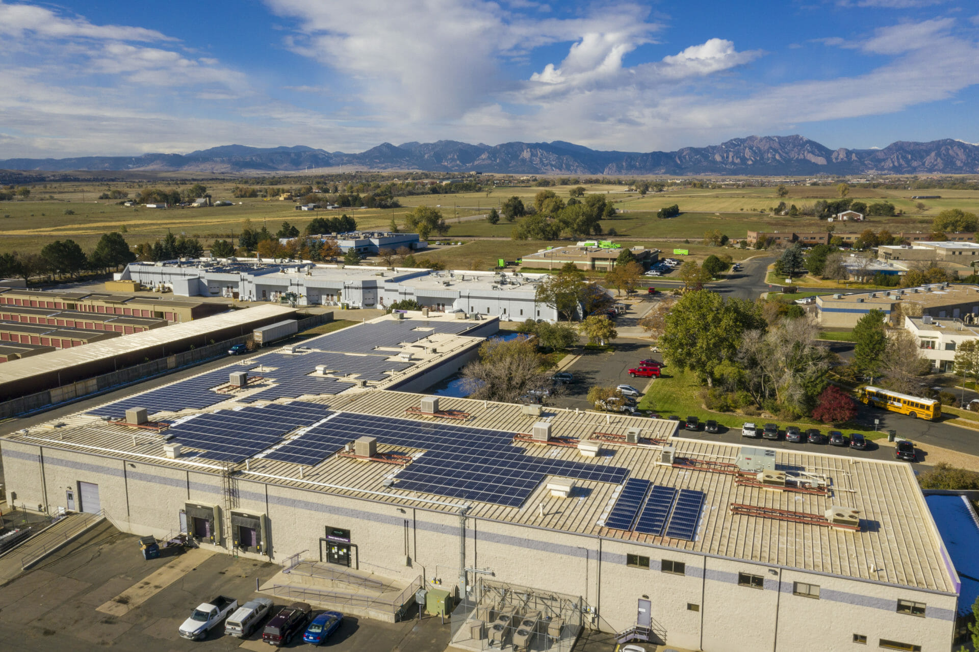 large rooftop commercial solar panel array with colorado mountains in background