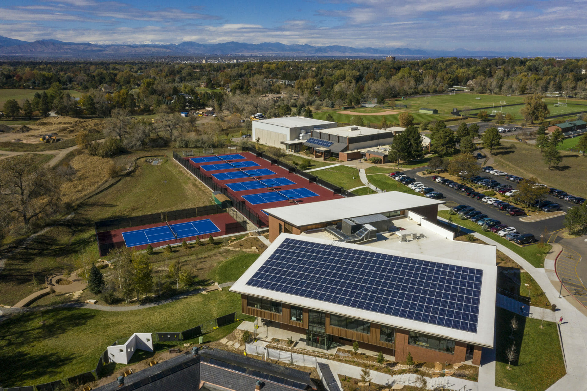 commercial solar panels on school in englewood colorado with playing fields and mountains in background