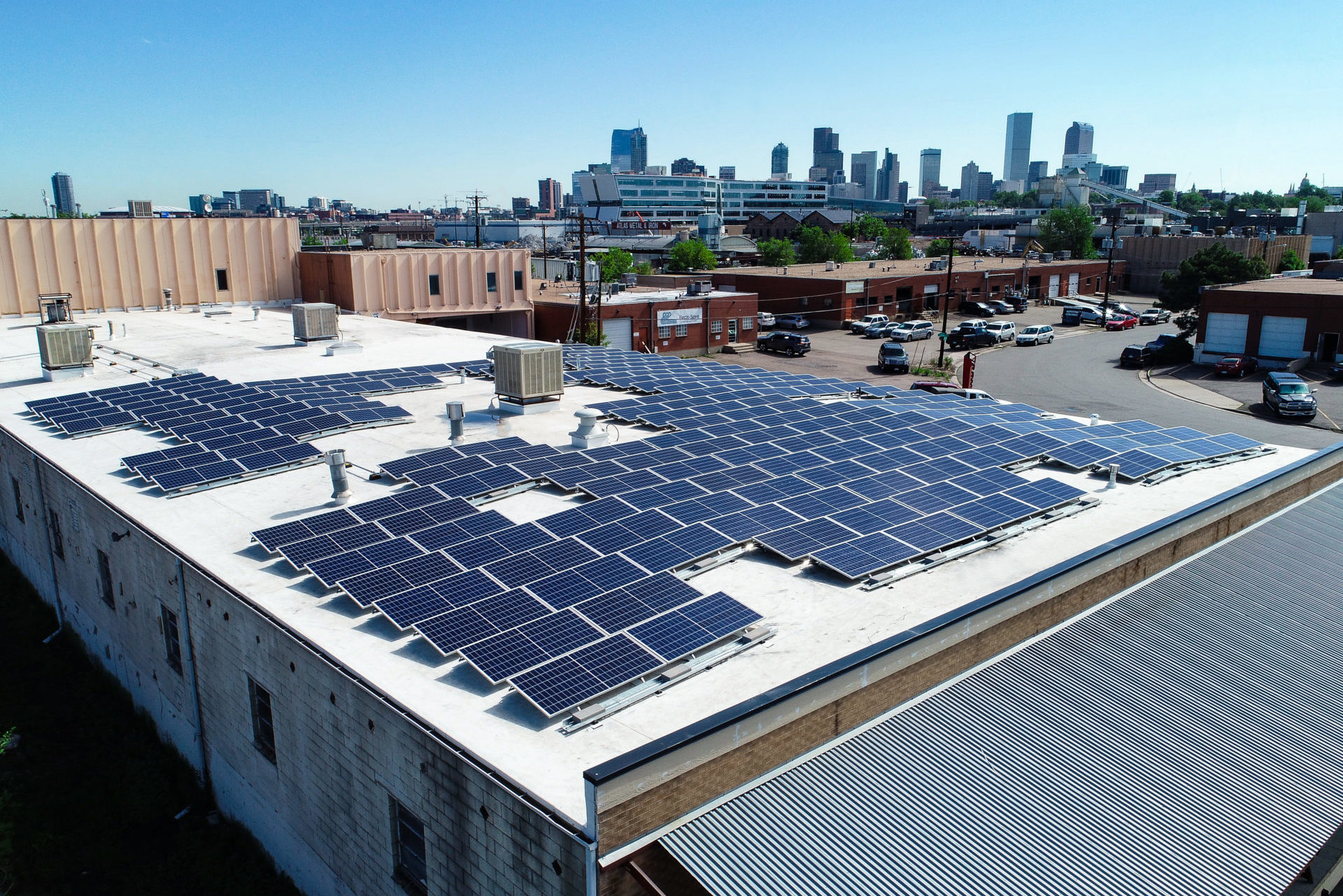 commercial solar panel installation with denver skyline in background