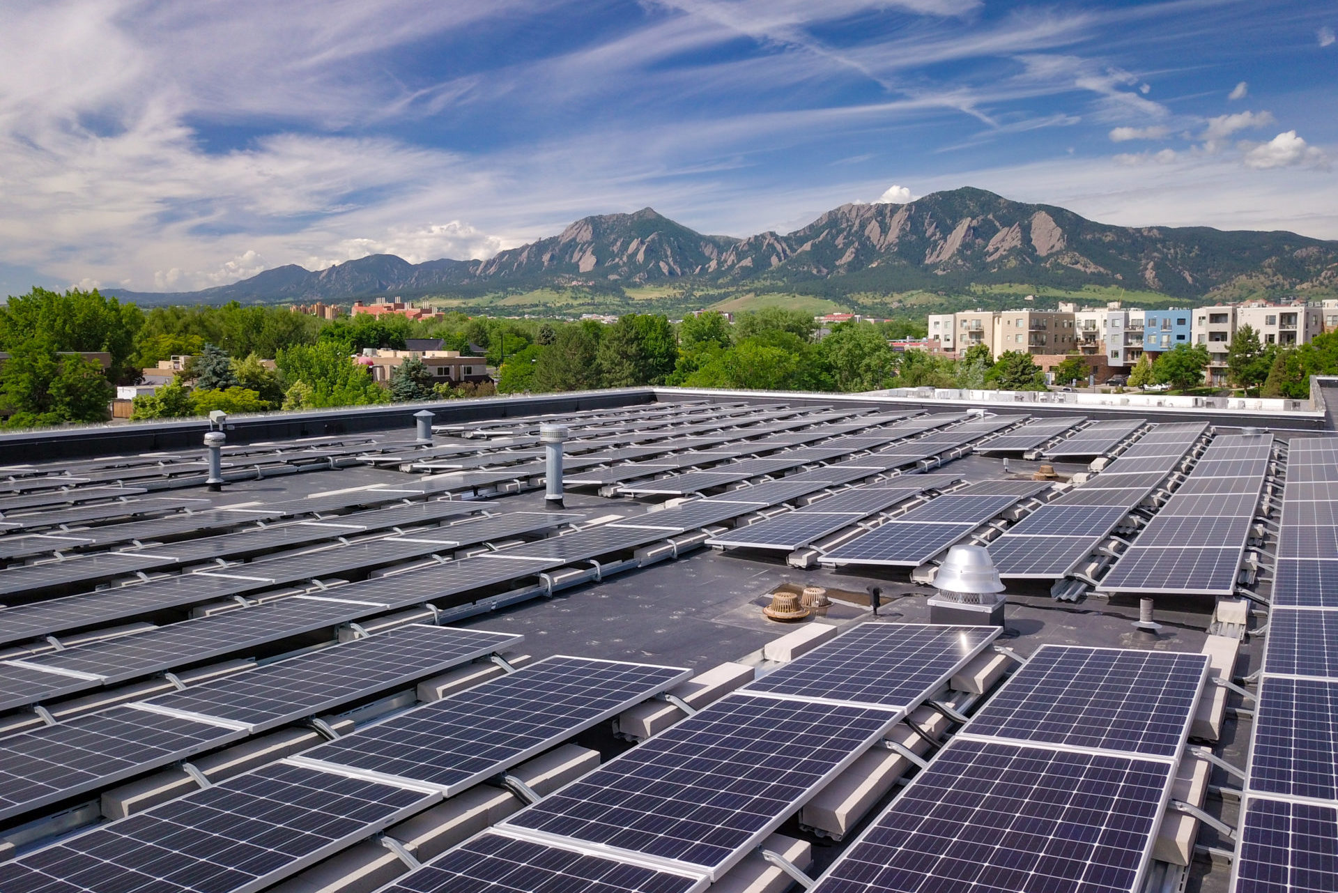 rooftop solar panels with boulder flatirons in background