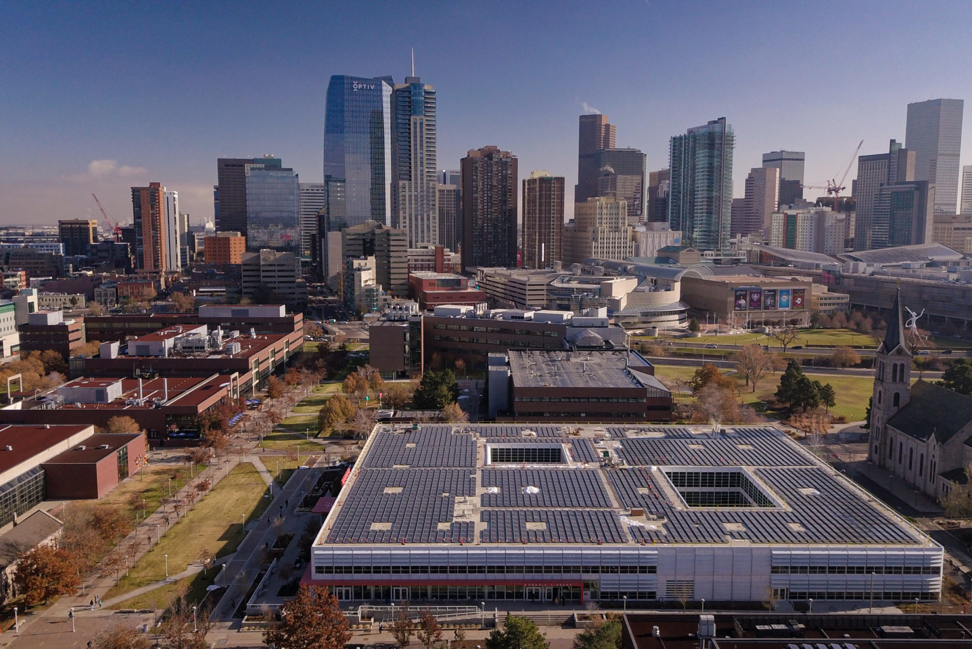 rooftop solar array with denver colorado skyline in background