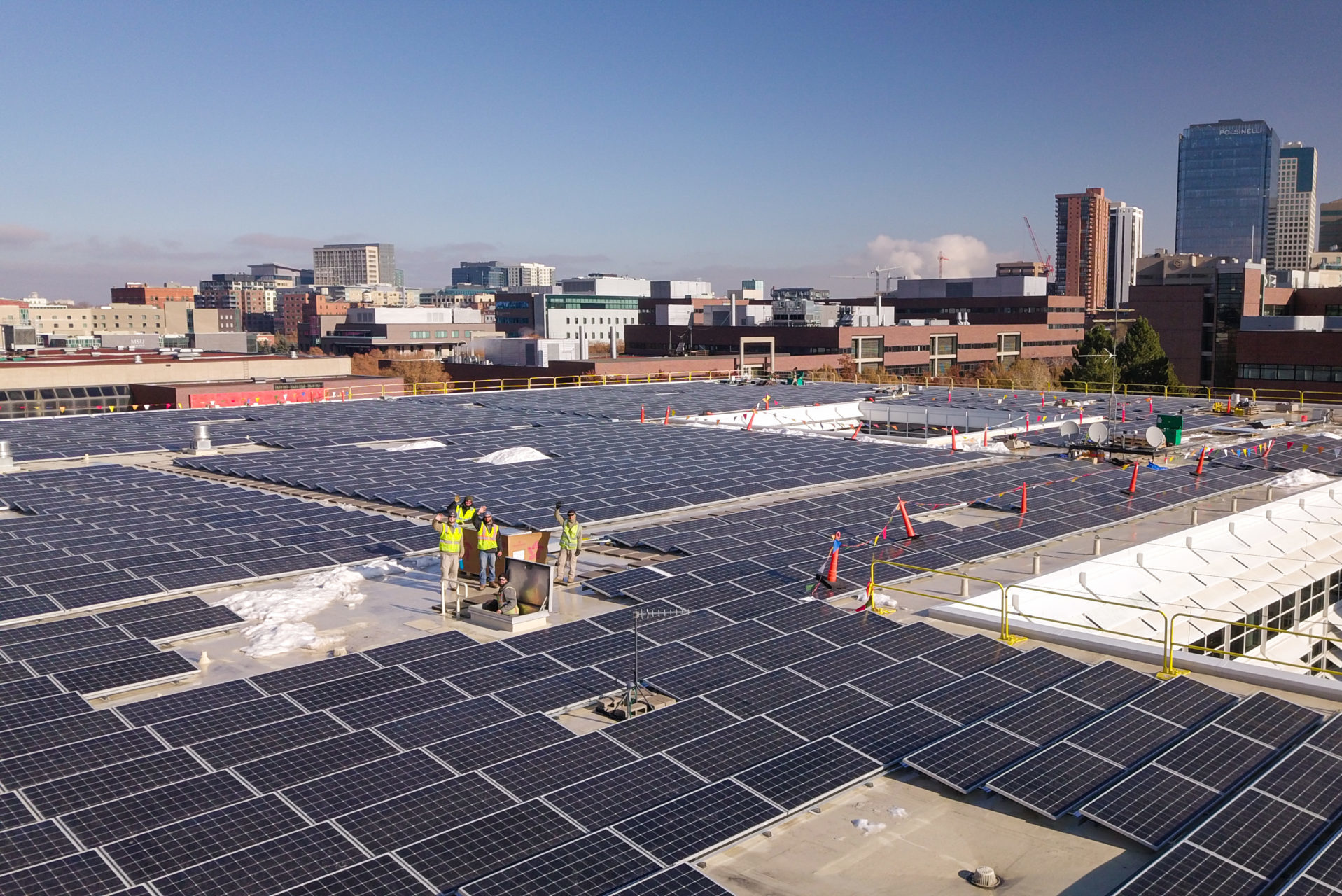 denver rooftop solar array with workers waving
