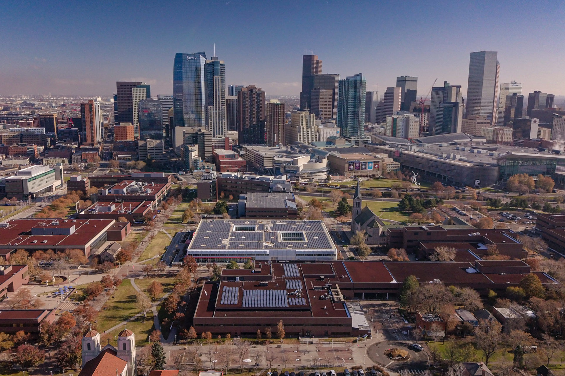 solar panels on rooftop with denver skyline in background
